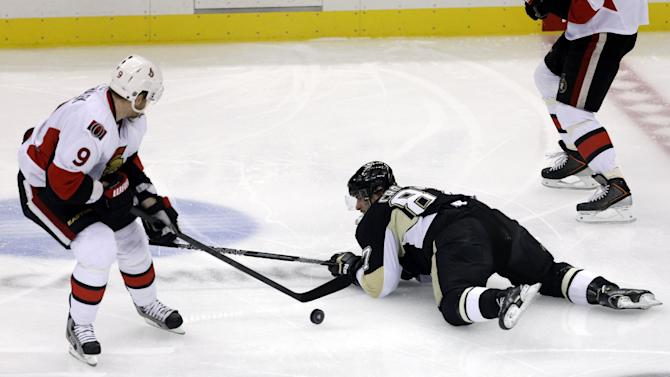 Pittsburgh Penguins' Sidney Crosby (87) falls and loses control of the puck to Ottawa Senators' Milan Michalek (9) during the first period in Game 5 of the Eastern Conference semifinals in their NHL hockey Stanley Cup playoffs series, Friday, May 24, 2013, in Pittsburgh. (AP Photo/Gene J. Puskar)