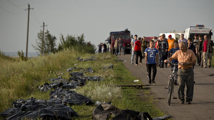 Bodies of victims are placed in plastic sacks by the side of the road at the crash site of Malaysia Airlines Flight 17 near the village of Hrabove, eastern Ukraine, Saturday, July 19, 2014. World leaders demanded Friday that pro-Russia rebels who control the eastern Ukraine crash site of Malaysia Airlines Flight 17 give immediate, unfettered access to independent investigators to determine who shot down the plane. (AP Photo/Vadim Ghirda)