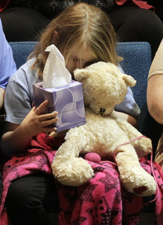 "Lauren Higginson, a student on  Charles ""Chuck"" Poland's bus, hugs her teddy bear during the ceremony to honor Poland at the Ozark Civic Center on Sunday, Feb. 3, 2013, in Ozark, Ala. (AP Photo/Butch"