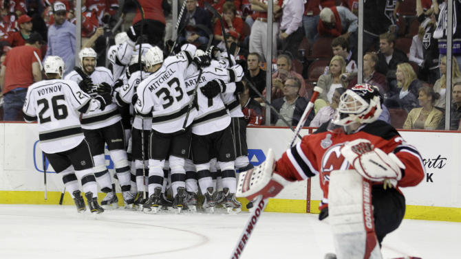 New Jersey Devils' goalie Martin Brodeur gets up from the ice after as the Los Angeles Kings celebrate their winning goal during the overtime period of Game 1 of the NHL hockey Stanley Cup finals Wednesday, May 30, 2012  in Newark, N.J.  The Kings won the game 2-1. (AP Photo/Julio Cortez)