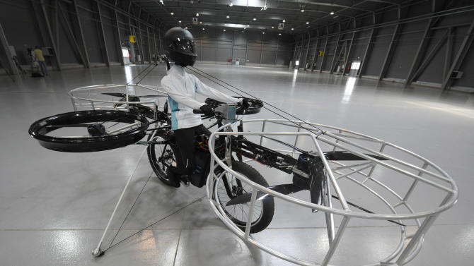The remote-controlled Flying Bike with a test dummy is ready for its during presentation fly in Prague on Wednesday, June 12, 2013.   Three Czech companies have teamed up to make a prototype of an electric bicycle that can fly. Controlled remotely, the bike carrying a figurine successfully took off Wednesday inside a large exhibition hall in Prague and landed safely after a five-minute flight.(AP Photo/CTK, Stanislav Zbynek)  SLOVAKIA OUT