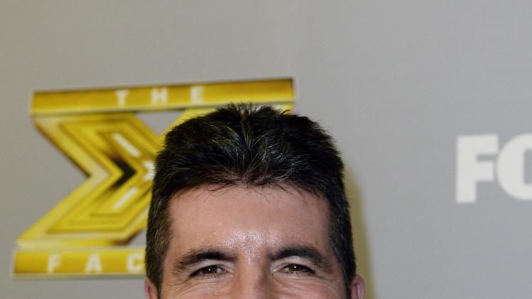 "Simon Cowell poses backstage after ""The X Factor "" finale in Los Angeles"
