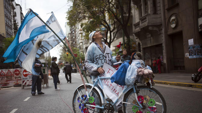 A supporter of Argentina's President Cristina Fernandez arrives in a bicycle decorated with Argentine flags at the Favaloro Hospital in Buenos Aires, Argentina, Wednesday, Oct. 9, 2013. The doctors who removed a blood clot from the brain of Argentina's president on Tuesday say she's improving without complications. (AP Photo/Victor R. Caivano)