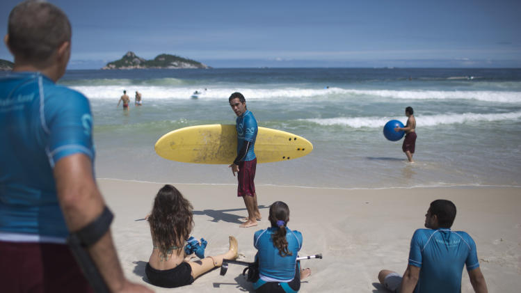 In this March 16, 2013 photo, AdaptSurf co-founder and physical therapist Luiz Phelipe Nobre, center, teaches surfing lessons at Barra da Tijuca beach in Rio de Janeiro, Brazil. AdaptSurf is a Rio-based non-governmental organization that aims to make beaches accessible to the disabled and encourage them to practice water sports. (AP Photo/Felipe Dana)