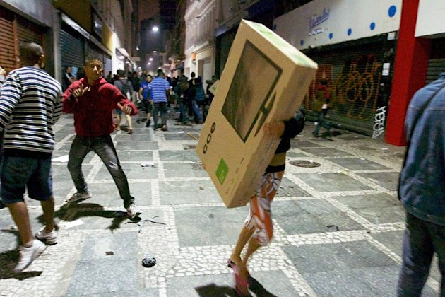 A looter carries away a TV set during clashes in Sao Paulo, Brazil on June 18, 2013