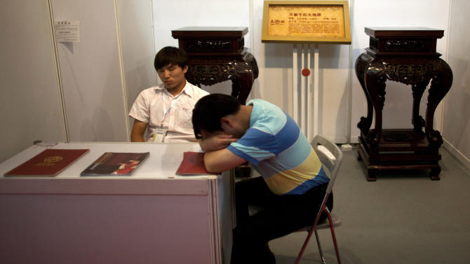 Furniture traders nap while waiting for customers during a consumer products exhibition in Beijing Friday, July 13, 2012. China's economic growth slowed to a new three-year low in the latest quarter as exports and consumer spending weakened. (AP Photo/Alexander F. Yuan)