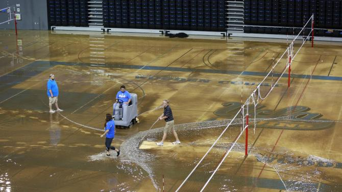 Workers try to clear water from the floor of Pauley Pavillion on the UCLA campus in the Westwood section of Los Angeles