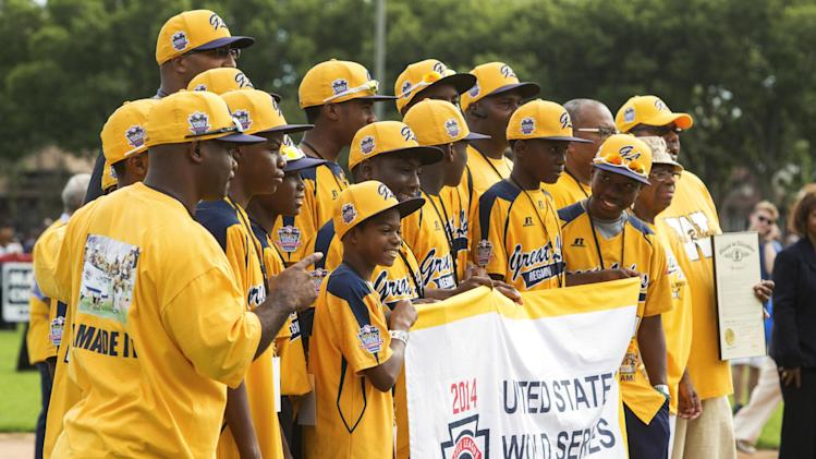 The Jackie Robinson West All Stars baseball team stand on the field at their hometown ballpark in Chicago during a rally Wednesday, Aug. 17, 2014, before they headed out for a parade to honor their play in the Little League World Seris in South Williamsport, Pa. The all-black team claimed the U.S. title in the Little League World Series