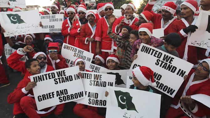 Pakistani Christians dressed as Santa Claus hold posters to condemn Tuesday's Taliban attack on a military-run school in Peshawar, as they take part in demonstration Sunday, Dec. 21, 2014 in Karachi, Pakistan. The attack shocked the nation and prompted a massive military response in the tribal regions along the Afghan border, longtime strongholds of both foreign and local militants. (AP Photo/Fareed Khan)