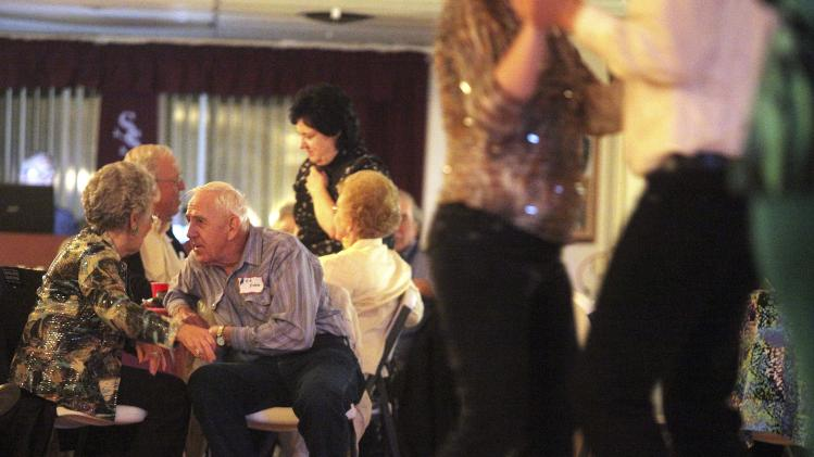 In this April 13, 2013 photo, Elynor Stagen, of Gibson City, Ill., talks with Ed Erbes, of Subledte, Ill., during a Singles in Agriculture social event at the Silver Spur Dance and Reception Hall, in East Moline, Ill. Singles in Agriculture is a group for single farmers seeking a social life or even a spouse. Chapters are active in 11 farm states in the Midwest and West, each of which holds three to six social events a year. (AP Photo/Matthew Holst)