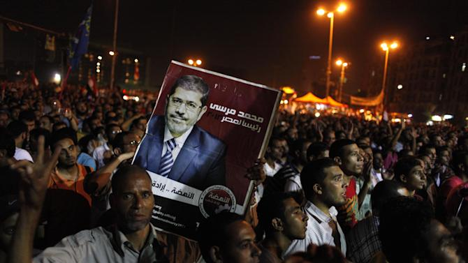 """Egyptian Muslim Brotherhood supporters chant slogans and one carries a poster with a picture of presidential candidate, Mohammed Morsi and Arabic that reads """"Mohammed Morsi, president for Egypt, revival is the will of the people,"""" during an anti-ruling military council demonstration in Tahrir Square, Cairo, Egypt Wednesday, June 20, 2012. Authorities delayed Thursday's planned announcement of the winner of Egypt's presidential election, likely for several days, hiking tension as allegations of fraud swirled and each candidate declared he was the victor. (AP Photo/Nasser Nasser)"""