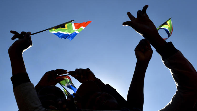 People hold South African flags as they attend 20-year Democracy Anniversary celebrations at the government's Union Building in Pretoria, South Africa, Sunday, April 27, 2014. The day marks the end of the apartheid era when all races went to the polls to cast their votes in historic 1994 elections. (AP Photo)