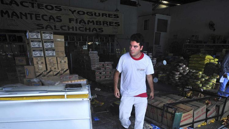 An employee walks in a ransacked shop in the northern Argentine province of Tucuman