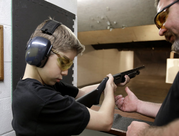 In this Sunday, May 19, 2013, photo, Dan Blackford, right, shows Rory Strain, 12, how to hold a shotgun at a shooting range Sunday, May 19, 2013, in Houston. Strain lives in the northwest Houston community of Oak Forest, the first residential area being trained and equipped by a nonprofit that is giving away free shotguns to single women and neighborhoods with high crime rates. (AP Photo/Pat Sullivan)