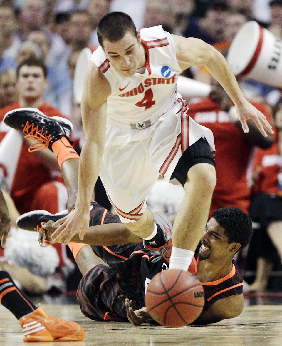 Ohio State guard Aaron Craft (4) escapes the defense of Cincinnati guard Jaquon Parker, rear, in the first half of an East Regional semifinal game in the NCAA men's college basketball tournament, Thursday, March 22, 2012, in Boston. (AP Photo/Michael Dwyer)
