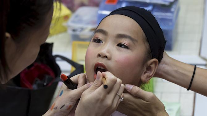 Peony Chu, a five-year-old, receives make up before she takes part in a Bun Festival parade at Hong Kong's Cheung Chau island