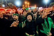 <p>Shiite Muslims gather outside the shrine of Imam Abbas in Karbala early on Sunday. Throngs of pilgrims beat their chests and some used swords to make cuts on their heads as a sign of mourning for Imam Hussein, grandson of the Prophet Mohammed who was killed in 680 AD by the armies of the caliph Yazid.</p>