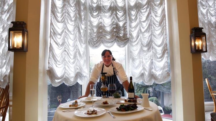 In this Dec. 7, 2012 photo, executive chef Kristin Butterworth poses for a photograph with her reveillon menu at the Grill Room of the Windsor Court Hotel in New Orleans. Roughly 50 restaurants in New Orleans are reviving an old Creole custom called reveillon, which stems from the old French tradition of eating a lavish meal after midnight Mass on Christmas Eve. (AP Photo/Gerald Herbert)