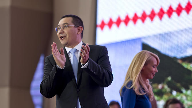 Romania's Prime Minister Victor Ponta applauds as his wife Daciana, right, walks by as they arrive for an electoral rally at the National Arena stadium in Bucharest, Romania, Saturday, Sept. 20, 2014. Ponta launched his bid for the Romanian presidency in the upcoming Nov. 2 presidential elections in front of about 50,000 supporters bussed into the Romanian capital from all over the country by the ruling Social Democrat party.  (AP Photo/Vadim Ghirda)