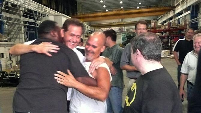 """In this photo provided by JWF Industries, CEO Bill Polacek, second left, hugs workers at the Johnstown, Pa. plant on Aug. 16, 2012 after the metal manufacturer for the defense, oil and gas industries voted 194-38 against joining the International Association of Machinists and Aerospace Workers. Polacek, the son of a union steelworker, appealed to his workers, saying he could point in every direction to unionized companies that were vacant or torn down. """"If the union can promise you job security, why are all these companies not here anymore?"""" he says he told them. (AP Photo/JWF Industries)"""
