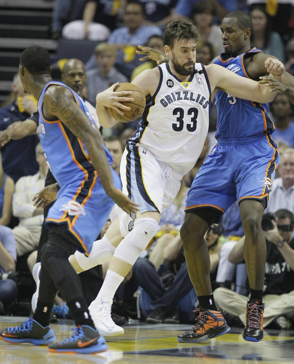 Memphis Grizzlies' Marc Gasol (33), of Spain, charges between Oklahoma City Thunder's DeAndre Liggins, left and Serge Ibaka, right, during the first half of Game 3 in a Western Conference semifinal NBA basketball playoff series in Memphis, Tenn., Saturday, May 11, 2013. (AP Photo/Danny Johnston)