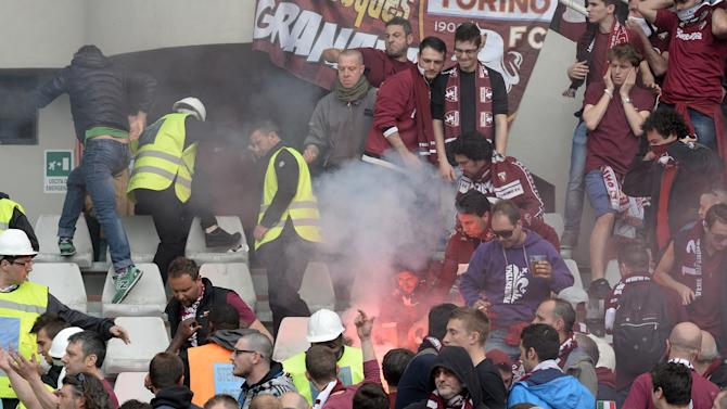 Smoke billows among Torino supporters prior to a Serie A soccer match between Torino and Juventus, at the Turin Olympic stadium, Italy, Sunday, April 26, 2015. Fireworks have exploded inside the stadium during the Torino-Juventus derby, injuring multiple fans. Before the match, Torino fans attacked the bus carrying Juve's players to the stadium, breaking a window. (AP Photo/Massimo Pinca)