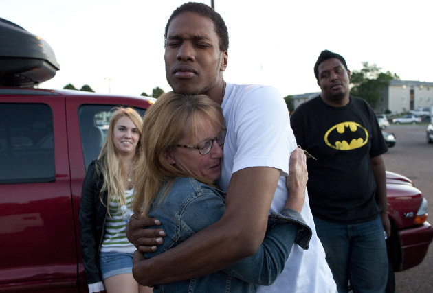 Judy Goos, center left, hugs her daughter's friend, Isaiah Bow, 20, while eyewitnesses Emma Goos, 19, left, and Terrell Wallin, 20, right, gather outside Gateway High School where witnesses were b