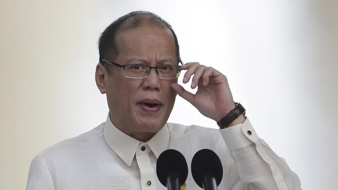 Philippine President Benigno Aquino III adjusts his glasses as he delivers his speech during rites to mark the 115th Philippine Independence Day at Liwasang Bonifacio, a sqaure named after Filipino revolutionary leader Andres Bonifacio, in Manila, Philippines on Wednesday June 12, 2013. Aquino III vowed Wednesday his country will not back down from any challenge to its sovereignty and territory amid a sea dispute with China. (AP Photo/Aaron Favila)