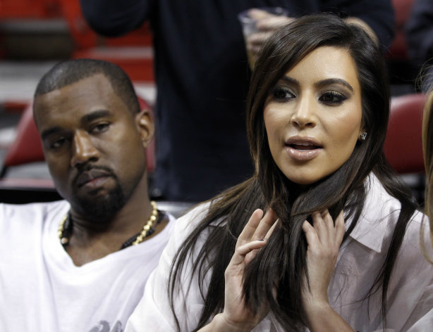 "FILE - Kim Kardashian, right, and Kanye West, left, are shown before an NBA basketball game between the Miami Heat and the New York Knicks in this Dec, 6, 2012 file photo taken in Miami. The rapper Kanye West announced at a concert Sunday night Dec. 30, 2012 that his girlfriend is pregnant. He told the crowd of more than 5,000 at the Ovation Hall at the Revel Resort in song form: ""Now you having my baby."" ( AP Photo/Alan Diaz, File)"