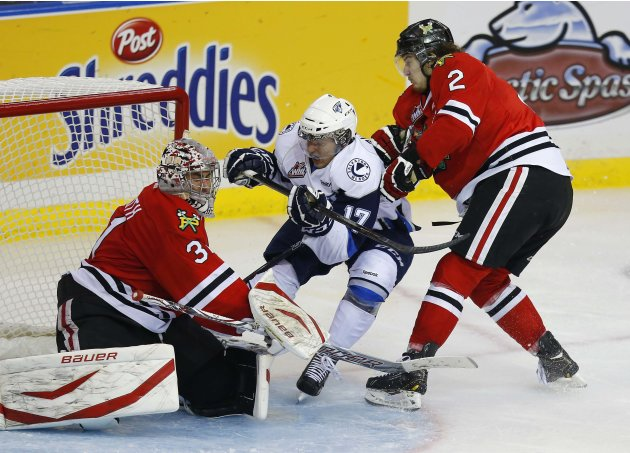 Saskatoon Blades' Zajac gets pushed into Portland Winterhawks' Carruth by Rutkowski during the Memorial Cup Canadian Junior Hockey Championships in Saskatoon.