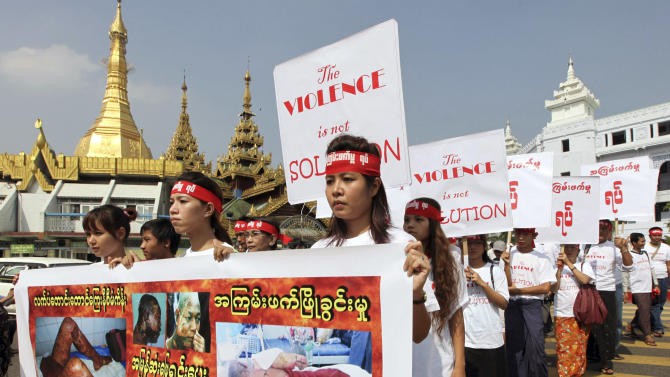 "Holding placards which read ""The violence is not solution,"" activists march in protest against recent violence in central Myanmar, Monday, Dec. 10, 2012, in downtown Yangon, Myanmar. About 50 activists staged the protest to mark International Human Rights Day. (AP Photo/Khin Maung Win)"