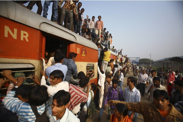 Commuters struggle to board a train at Noli railway station in Uttar Pradesh
