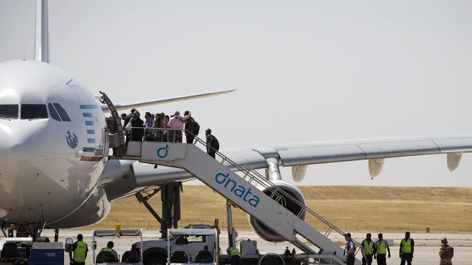 Iraqi Christian refugees board a plane bound for Paris from Arbil in northern Iraq as they flee violence in their country on August 21, 2014