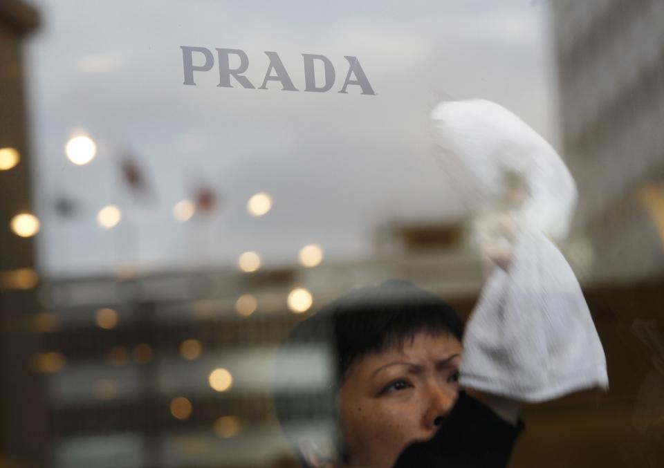 A worker cleans the front door of a Prada store in Hong Kong Sunday, June 12, 2011. Prada and its bankers say an international roadshow to promote the Italian fashion house's upcoming Hong Kong IPO is going well despite recent turmoil in world stock markets. Prada is selling some 423.3 million shares in an initial public offering this month. (AP Photo/Vincent Yu)
