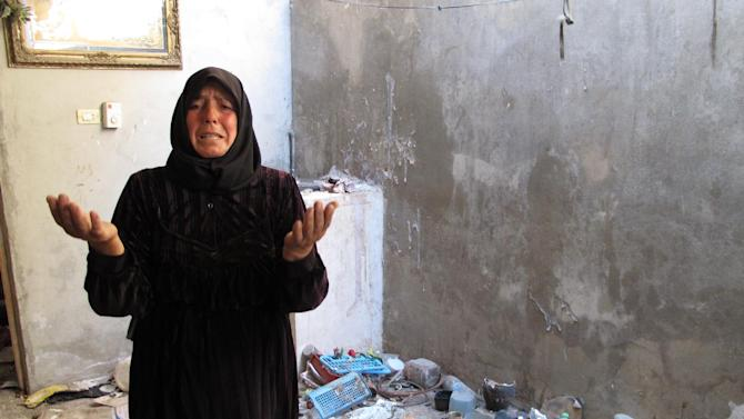 In this photo from Sunday, Aug. 5, 2012, Fatoum Obeid, 50, stands in a pile of trash left by Syrian soldiers who occupied her home in Atarib, Syria. In recent months rebels have seized a huge swath of territory in northern Syria, giving them a freedom to move and organize unprecedented in the 17-month conflict. (AP Photo/Ben Hubbard)