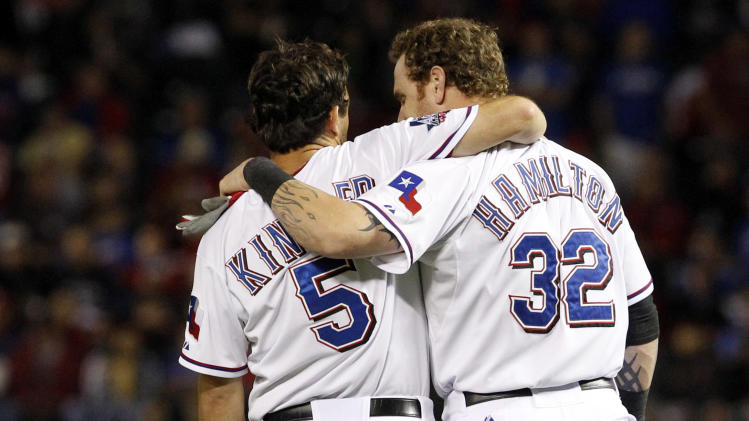 Texas Rangers second baseman Ian Kinsler (5) and center fielder Josh Hamilton (32) embrace during the ninth inning of an American League wild-card playoff baseball game against the Baltimore Orioles on Friday, Oct. 5, 2012, in Arlington, Texas. Baltimore won 5-1. (AP Photo/LM Otero)