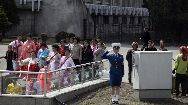 A female traffic coordinator salutes near North Korean women dressed in traditional attire walking into an underpass in Pyongyang, North Korea, Wednesday, April 11, 2012. (AP Photo/Ng Han Guan)