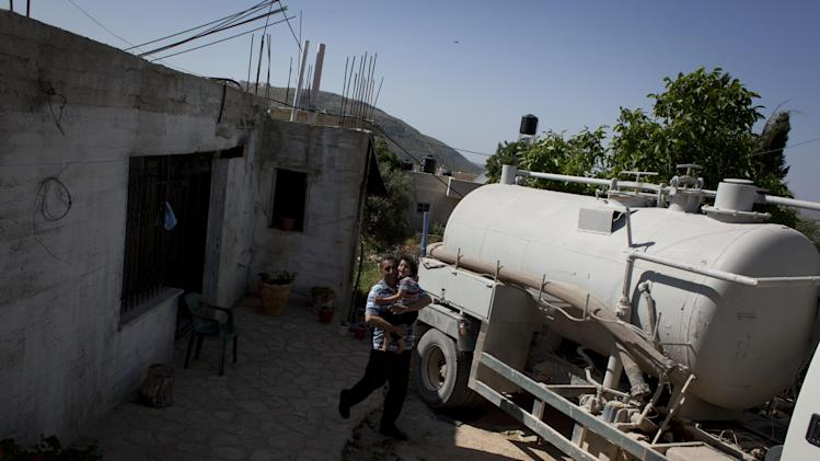 In this April 17, 2014 photo, a Palestinian landlord carries his daughter by a sewage tank vehicle that he rents to vacuum his house's underground wastewater storage container, at the Palestinian village of Silwad, adjacent to the Israeli settlement of Ofra, north of the West Bank city of Ramallah. (AP Photo/Nasser Nasser)