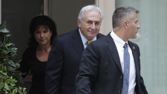 Former IMF head Dominique Strauss-Kahn, center, and his wife, Anne Sinclair, leave his rented house escorted by security, Wednesday, July 6, 2011, in New York.  (AP Photo/Seth Wenig)