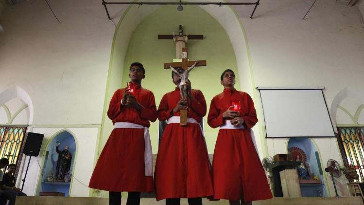 Altar boys hold up a crucifix and lamps as they take part in a Good Friday prayer at a church in Kolkata