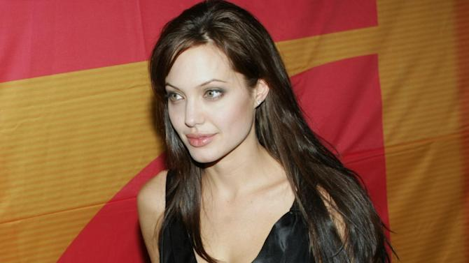 """FILE- In this Aug. 13, 2003 file photo, actress Angelina Jolie arrives at the Mathaeser cinema in Munich, Southern Germany, to attend the German premiere of her latest movie """"Lara Croft Tomb Raider: The Cradle of Life."""" Less than two weeks after Jolie had a double mastectomy to avoid breast cancer, her aunt has died from the disease. Jolie's aunt Debbie Martin died at age 61 Sunday in a San Diego-area hospital, her husband Ron Martin tells The Associated Press. Debbie Martin was the younger sister of Jolie's mother Marcheline Bertrand, whose own death from cancer in 2007 inspired the surgery that Jolie described in a May 14 New York Times op-ed. (AP Photo/Uwe Lein, File)"""