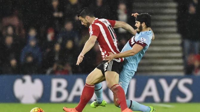 West Ham United's James Tomkins in action with Southampton's Graziano Pelle