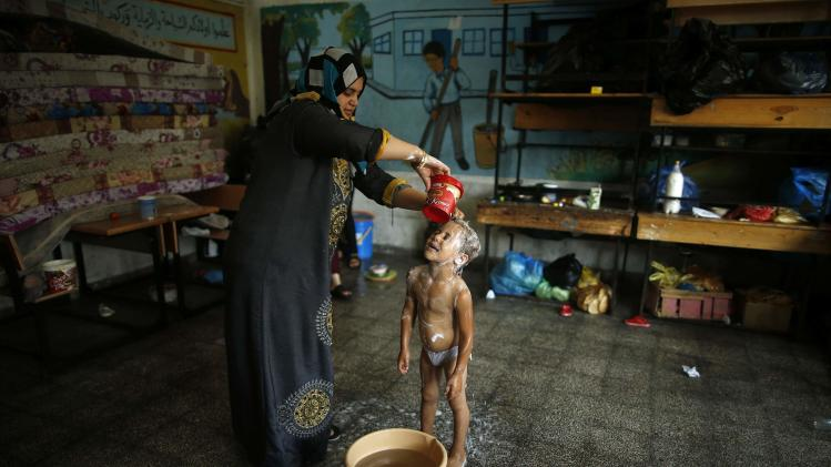 A Palestinian woman, who fled house during Israeli ground offensive, bathes son at United Nations-run school in Gaza City