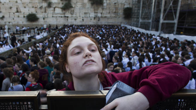 "A Jewish orthodox women follows a prayer organized by the ""Women of the Wall"" organization, not pictured, at the Western Wall, the holiest site where Jews can pray in Jerusalem's old city, Friday, May 10, 2013. The ""Women of the Wall"" group has been holding monthly prayer services on the first day of the Hebrew month at the Western Wall in Jerusalem for more than two decades, wearing prayer shawls and performing religious rituals reserved for men under Orthodox Judaism. Accused by ultra-Orthodox leaders of violating ""local custom"" at the holy site, many members have been arrested. On Friday the tables were turned because of the court ruling. Police protected the women and arrested three ultra-Orthodox men for disorderly conduct, police spokesman Micky Rosenfeld said. (AP Photo/Bernat Armangue)"