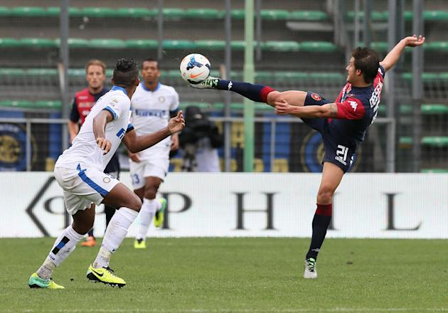 Cagliari's Daniele Dessena, right, reaches for the ball as Inter Milan's Juan watches, during the Serie A soccer match between Cagliari and Inter, at the Nereo Rocco Stadium in Trieste, Italy, Sunday,