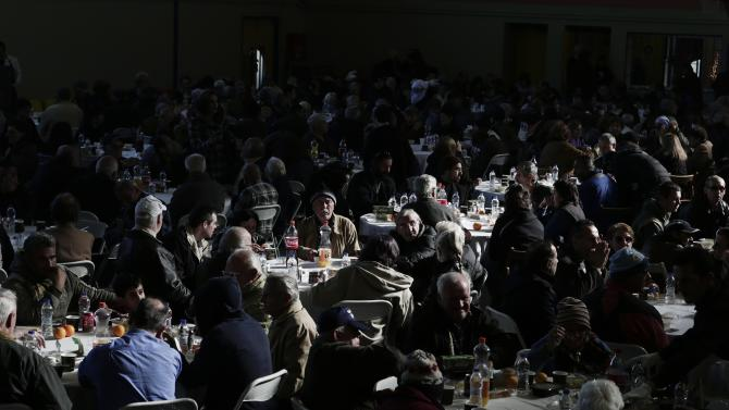 People receive a Christmas meal for the homeless and the poor at an indoor gym hall in Athens