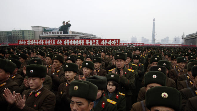 North Korean soldiers applaud near slogans honouring their leadership during  a mass rally organized to celebrate the success of a rocket launch that sent a satellite into space on Kim Il Sung Square in Pyongyang, North Korea, Friday, Dec. 14, 2012. As the U.S. led international condemnation of what it calls a covert test of missile technology, top North Korean officials denied the allegations and maintained the country's right to develop its space program. (AP Photo/Jon Chol Jin)