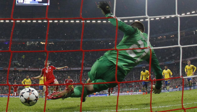 Arsenal's goalkeeper Lukasz Fabianski saves a shot from the penalty spot by Bayern's Thomas Mueller during the Champions League round of 16 second leg soccer match between FC Bayern Munich and