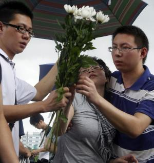 A grieving woman is assisted to lay flowers for victims of a high speed train crash at the crash site in Wenzhou, southeastern China's Zhejiang province, Friday, July 29, 2011.  Chinese Premier Wen Jiabao vowed Thursday to punish any corrupt person found responsible for Saturday's crash that killed at least 39 people and triggered public anger over its handling. (AP Photo/Ng Han Guan)