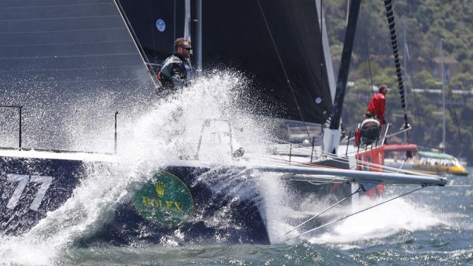 A crewman aboard Black Jack gets sprayed on the bow of their yacht alongside Comanche before the start of the Sydney to Hobart Yacht Race